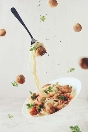 Flying food. Levitation of pasta fettuccine with meatballs, tomato sauce, basil on white concrete background