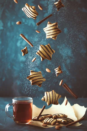 Falling cookies with hot tea. Levitation of gingerbread with chocolate sauce and cinnamon on dark background. Vertical composition Imagens