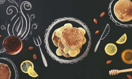 Stack of pancakes with banana, lemon and almond  on chalk board with drawings. Background