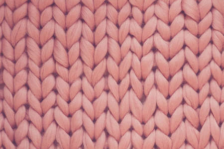 Texture of pink big knit blanket. Large knitting. Plaid merino wool. Top view