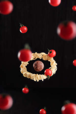 Flying food. Levitation of pasta fettuccine with meatball and tomatoes on black background. Concept of meatball as a planet and spaghetti as a ring system around a planet.
