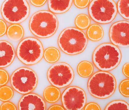 Milk bath with grapefruit and oranges slices. Top view. Flat lay. Fruits
