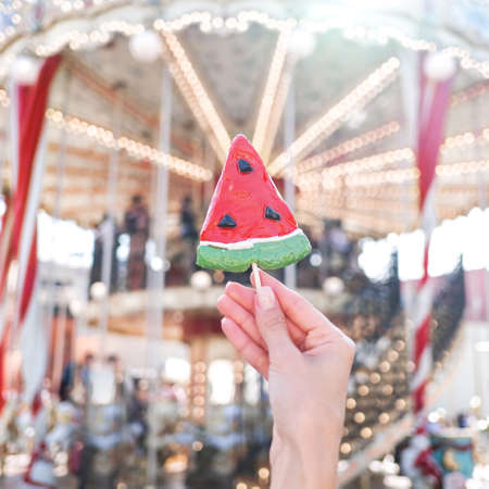 Hand holding a lollipop in watermelon shape, carousel on background Foto de archivo