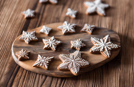 Set of homemade gingerbread on brown wooden background. Christmas cookies in stars shape.
