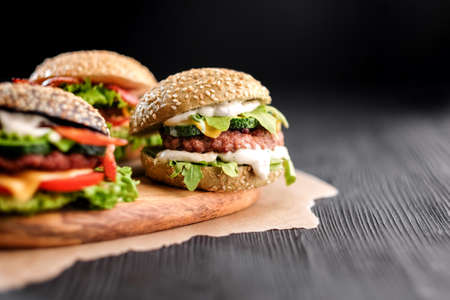 Three handmade burgers with beef, salad, cheese tomatoes, sesame seeds, bacon on black wooden table