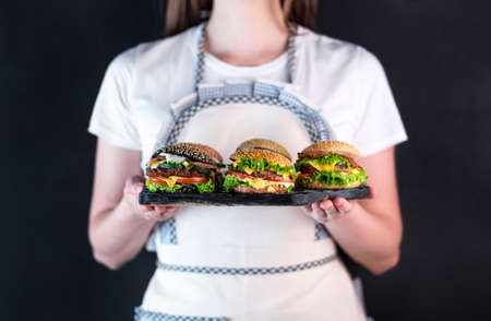 Woman in apron holding in her hands a tray with 5 burgers with different fillings