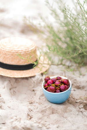 Picnic on beach, cherries in blue plate, straw hat on background Foto de archivo