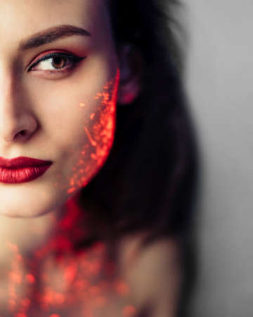 Woman with red glowing uv neon paint on her face and neck. Red lipstick. Brown hair. Fashion portrait Foto de archivo