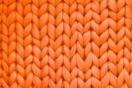 Textur der großen Strickdecke aus orangefarbener Wolle. Großes Stricken. Karierte Merinowolle. Ansicht von oben