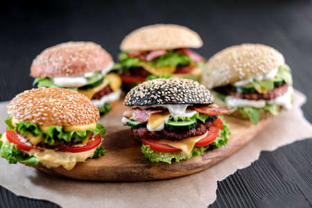 5 handmade burgers with beef, salad, cheese tomatoes, sesame seeds, bacon on wooden table Foto de archivo - 133743851