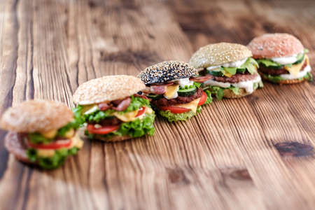 5 handmade burgers with beef, salad, cheese tomatoes, sesame seeds, bacon on wooden table