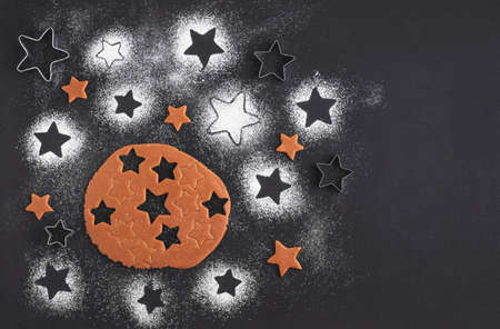 Gingerbread christmas cookies preparation. Top view. The Ingredients on a black table. Stars shape