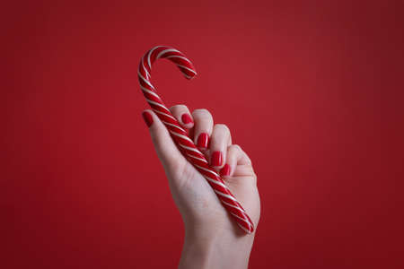 Womans hand with red manicure nails holding christmas candy cane on red background Foto de archivo