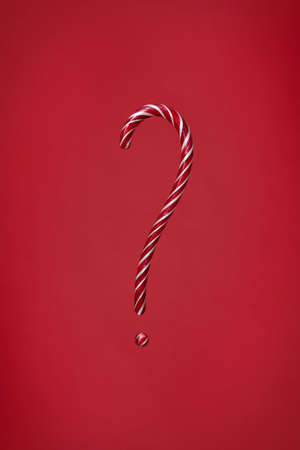 Candy cane question mark on red background. Christmas striped candie