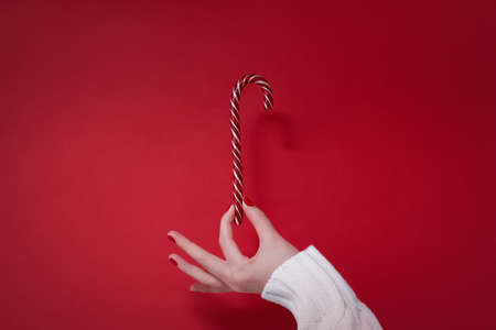 Womans hand in white sweater with red manicure nails holding christmas candy cane on red background