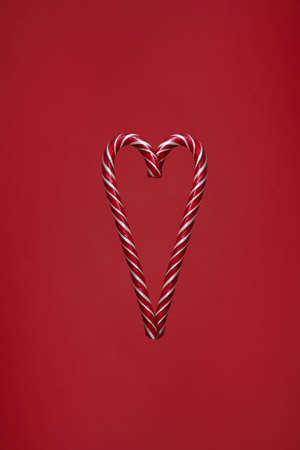 Candy canes in heart shape on red background