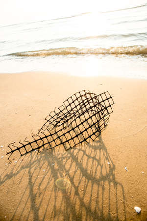 wire mess: Steel wire on the beach,A fish trap entangled in kelp washes ashore on the beach