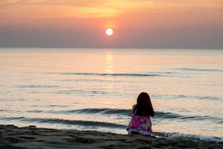 mujer mirando el horizonte: Niña sentada en la playa al atardecer.
