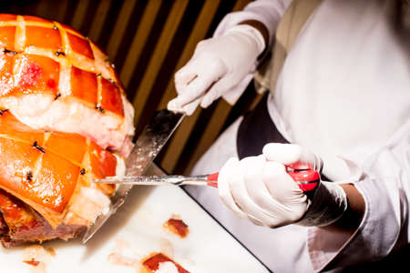 daniele: butchers hand while fast cuts a piece of raw ham, cut ham