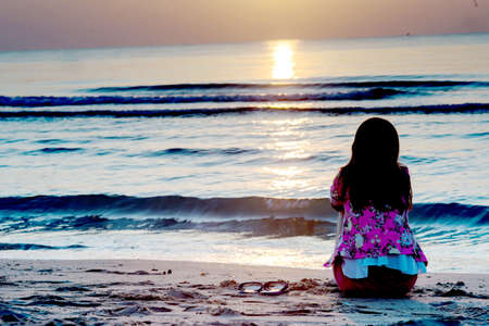 ser humano: Niña sentada en la playa al atardecer.