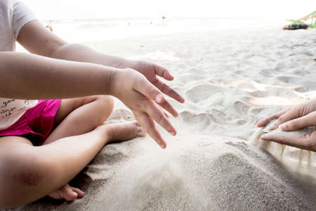 unedited: Childrens play sand, Young girl molds of sand on the beach.
