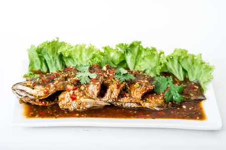 grouper: Crispy fry grouper is topped with chili sauce on white dish,fried grouper fish with sauce,
