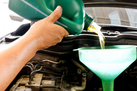 servicing: Car servicing mechanic pouring oil to engine Stock Photo