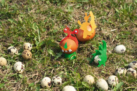 Some painted Easter eggs on the lawn. Joke photo with chiken and quail eggs, some of them decorated with cloth and toy eyes. Day light, shot on the green lawn in Spring. photo
