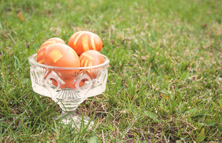 Some Easter eggs in crystal vase on a green lawn. Chicken eggs, natural color with lines. Day light, object on the right side of shot. Sunny day, side view. photo