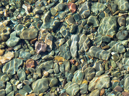 rocks water: Many underwater stones different forms and color. Daylight, close-up, limestones and some volcanic.