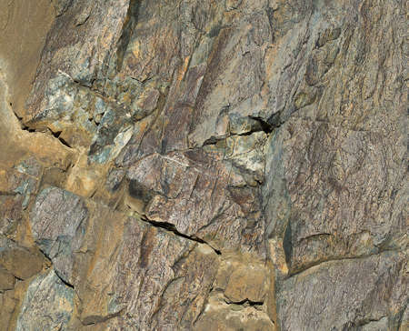 waterless: Surface of stone with crumpled craft paper texture and two coins in a crack. Daylight, close-up, volcanic by geology, texture.