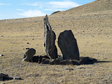 Two balbals with stone fences in steppe, sacred place. Ancient burial ground, late bronze age, Scythians tradition of burial. Steppe, Mountain Altai, daylight.