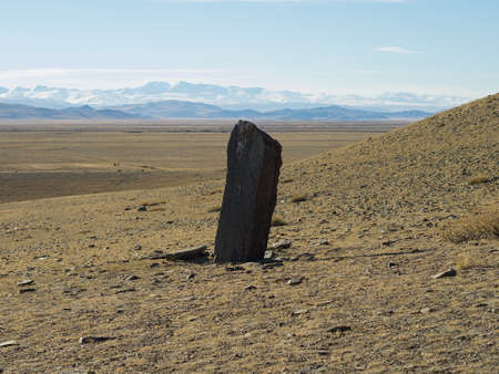 hitching post: Stone figure in the Steppe, sacred place. Proud menhir on the backdrop of the high mountains and steppe. Sightseeing area in Chuya steppe. Sacred place, daylight.