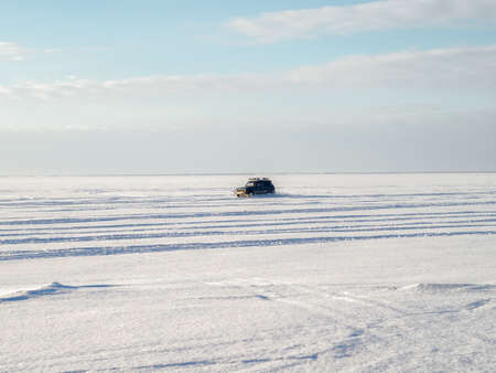 drifts: Car drifts on the snow and ice. Winter time, frosty weather, sunny day, city on horizon. Stock Photo