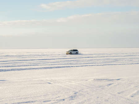 drifts: White jeep drifts on snow and ice. Winter time, frosty weather, sunny day, skyline. Stock Photo