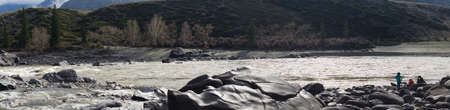 Katun river rapid, river banks, boulders and mountains. Three people on the bank. Sunny daylight, early spring and pink flowers on the bushes. Altai mountains. Reklamní fotografie
