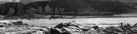 Katun river rapid, river banks, boulders and mountains. Three people on the bank. Sunny daylight, early spring and pink flowers on the bushes. Altai mountains. Panorama six shots, black and white variant. Reklamní fotografie