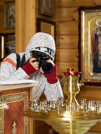 Woman photographer take pictures in the church. The Orthodox Church, winter. Icon in the background. Candle holder in the foreground.
