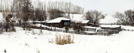Centennial house in the village. Russia, Altai region. House on the hill. Winter, Altai village. Smallholding, the buildings fences clouse to the house. Panorama of three frames. Reklamní fotografie