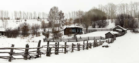 Centennial house in the village. Russia, Altai region. House on the hill. Winter, Altai village. Smallholding, the buildingsfences clouse to the house. Panorama of three frames.