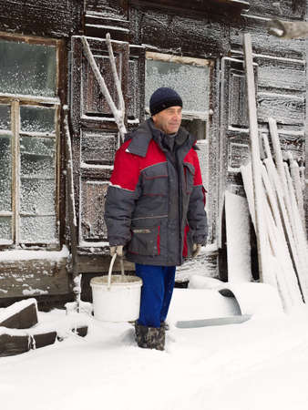 Farmer on the background of a century house. Altai village, Russia. Farmer holding a bucket with water. The morning after a snowstorm, the wall of house covered with snow. Some household things in the background. Morning, winter time.