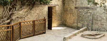 The open door in the stone fence. Moving from female to male half in the Khan Palace. Bakhchisaray Palace. Crimea, Russia. Panorama of four frames, sunny day.