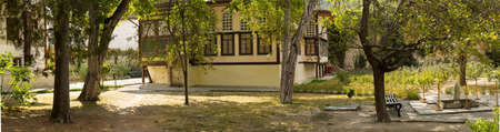 Patio around the Harem in the Khan Palace. Modern garden, antique fountain, ancient trees. Bakhchisaray Palace. Crimea, Russia. Panorama of six frames, sunny day. Reklamní fotografie