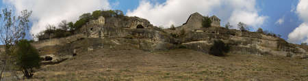 Chufut-Kale - medieval city-fortress in the Crimean Mountains that now lies in ruins. It is a national monument of Crimean Karaites culture close to Bakhchisaray. The front part of the wall of the cave city, two kenassa buildings on the front plan. Histor