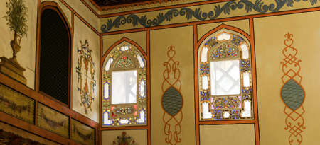 Unique colored stained glass windows of the upper row of the eastern wall of Sofa Hall (a Meeting Hall) of Bakhchisaray Palace, Crimea, Russia. Panorama of four frames, daylight, sun glare. Redakční