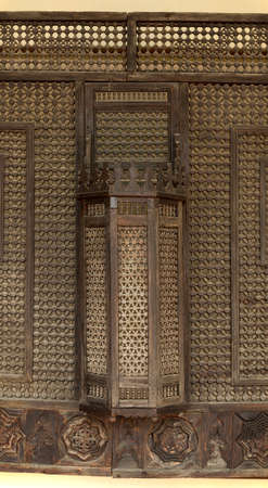 Part of wooden balcony lattice in the Harem. Through a lattice oriental beauties could look at the world without showing their face. Bakhchisaray Palace. Crimea, Russia. Panorama of three frames, daylight.