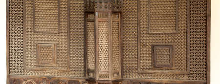 Part of wooden balcony lattice in the Harem of Khan. Through a lattice oriental beauties could look at the world without showing their faces. Bakhchisaray Palace. Crimea, Russia. Panorama of four frames, daylight.