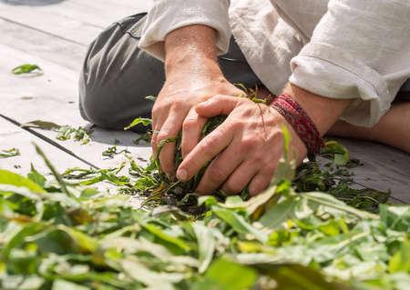 Male hands that crumple grass. Willowherb grass or Epilobium grass. Sunny day, sun glare, sunburnt skin, braided bracelet.