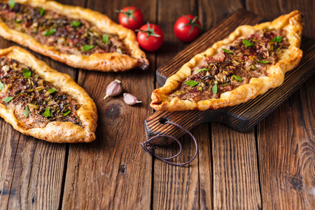 Turkish handmade pide lies on an old brown wooden table. Cherry tomatoes, parsley, lemon, hot pepper, garlic are on the table.