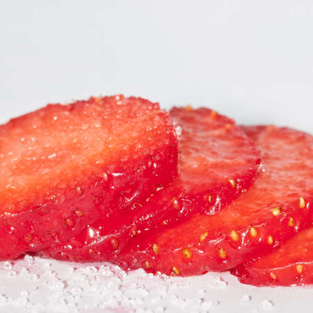 A row of sliced stawberry, covered in sugar.